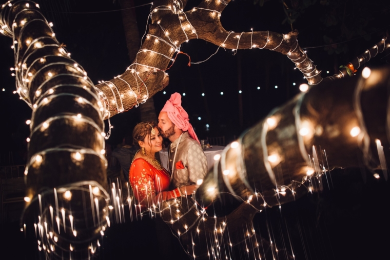 techniques of photography | fairy lights | reflection shot | groom is kissing the bride on the forehead